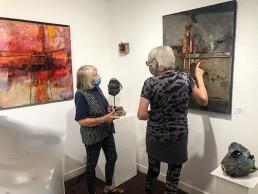 Anne Bradley (left) discusses her pieces on exhibit